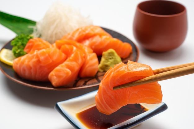 Sashimi, salmone, bacchette giapponesi e wasabi con piatto bianco isolato