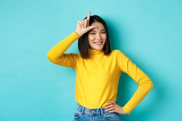 Ragazza asiatica sfacciata che deride la squadra persa, mostra il segno del perdente sulla fronte e sorride compiaciuta, essendo una vincitrice, in piedi su sfondo blu