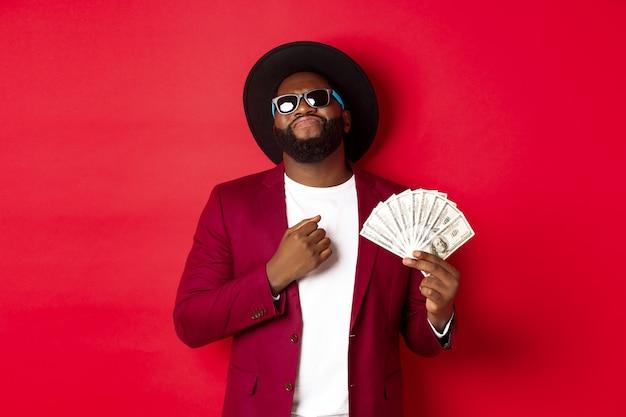 Sassy e cool uomo afroamericano in occhiali da sole e cappello, indicando se stesso e mostrando dollari, guardando fiducioso su sfondo rosso