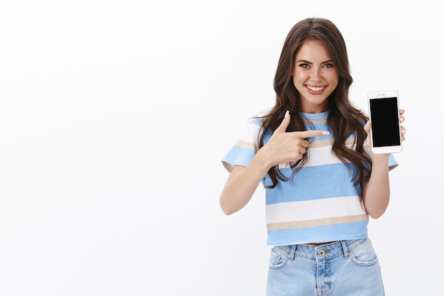 Sassy moderna bella donna europea in t-shirt, tenere lo smartphone introdurre un'app nuova di zecca, puntare il display del telefono cellulare, sorridere assertivo, consigliare il gioco, promuovere i social media su internet