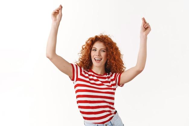 Sassy elegante fiducioso rossa zenzero ragazza ricci acconciatura ballare divertirsi godere festa alzando le mani alta vittoria celebrazione gesto trionfante ammiccante civettuolo sicuro di sé vantarsi successo