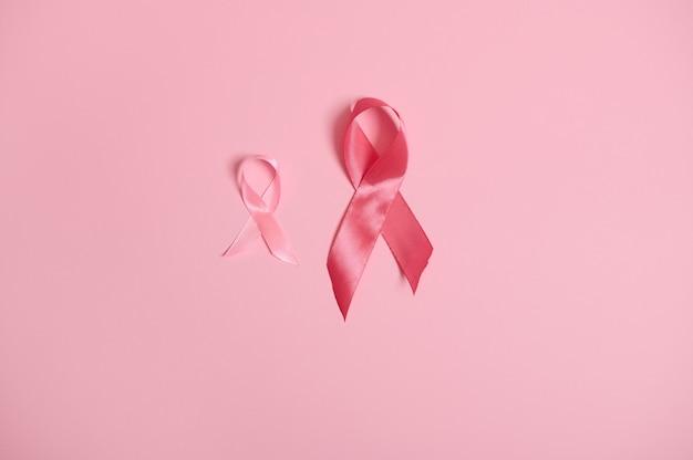 Consapevolezza dei nastri rosa satinati, simbolo internazionale del mese di sensibilizzazione sul cancro al seno in ottobre, sfondo rosa isolato, spazio copia. ottobre pink day, world cancer day, national cancer survivor say.