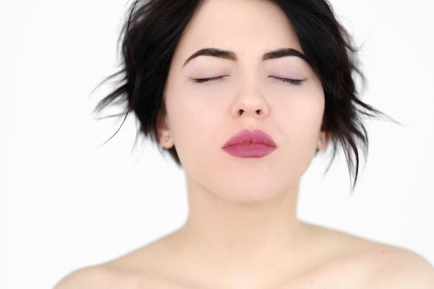 Soddisfazione piacere godimento gioia donna con gli occhi chiusi sul muro bianco.