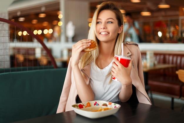Bella giovane donna soddisfatta con un sorriso che mangia un hamburger e che beve cola all'interno