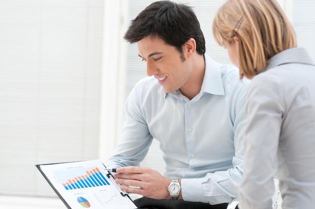 Uomo d'affari soddisfatto che mostra e che punta al grafico in crescita con il suo collega in ufficio