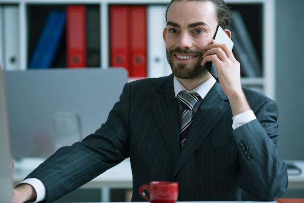 Uomo d'affari soddisfatto che parla sul telefono nell'ufficio