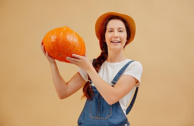 Una donna agricoltrice soddisfatta con un raccolto autunnale dai campi tiene una zucca matura su sfondo beige
