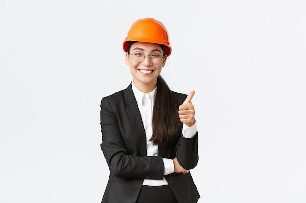 L'imprenditrice asiatica soddisfatta ispeziona l'impresa, è soddisfatta dei lavori di costruzione, mostra il pollice in su in segno di approvazione, sorride felice, dice ben fatto, buon lavoro, garantisce la costruzione in tempo