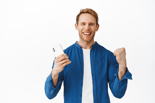 Soddisfatto bell'uomo che vince soldi sull'app del telefono cellulare, tiene in mano lo smartphone e grida sì con gioia e soddisfazione, festeggia, vince o raggiunge l'obiettivo nell'app, muro bianco