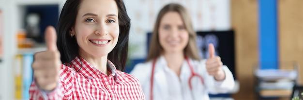 Giovane paziente adulta sorridente sana soddisfatta che mostra i pollici in su gesto insieme al medico