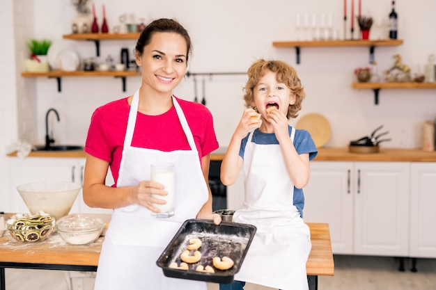 Ragazzino soddisfatto che mangia i biscotti al forno mentre sua madre tiene un bicchiere di latte e un vassoio con i biscotti
