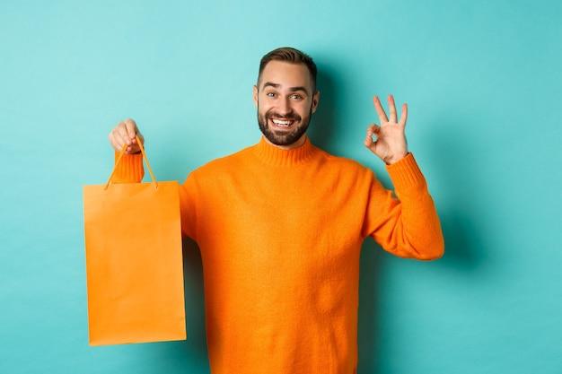 Cliente maschio soddisfatto che mostra borsa della spesa arancione e segno giusto, consigliando negozio, sorridendo soddisfatto, in piedi su sfondo turchese.