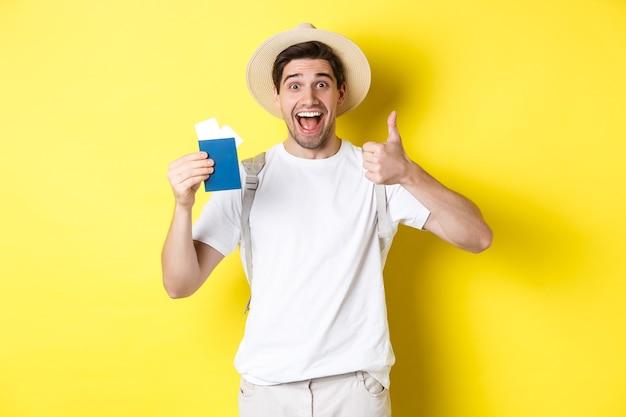 Turista maschio soddisfatto che mostra il passaporto con i biglietti e il pollice in su, raccomandando la compagnia di viaggi, in piedi sopra il muro giallo
