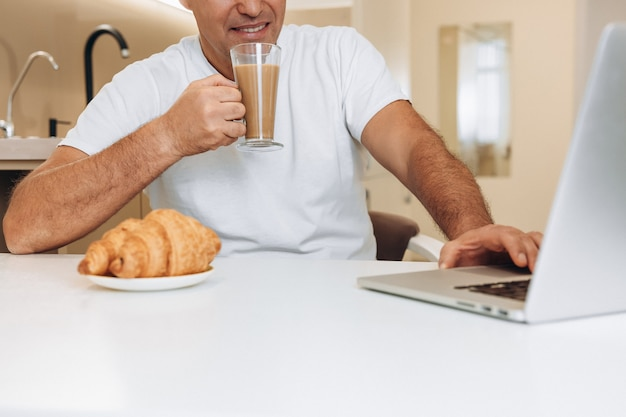L'uomo soddisfatto beve latte o caffè con latte e usa il suo laptop moderno.