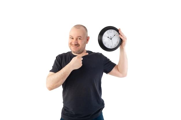 Un uomo soddisfatto in maglietta tiene in mano un grande orologio