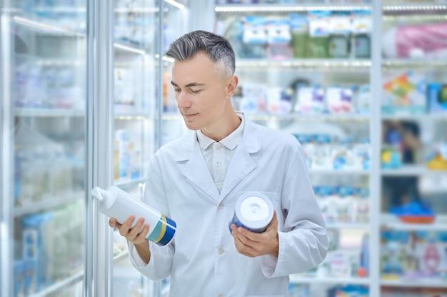 Uomo soddisfatto in camice bianco che tiene prodotti medici