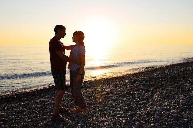 Uomo e donna soddisfatti stanno vicini, si abbracciano e si guardano al tramonto sulla spiaggia del mare
