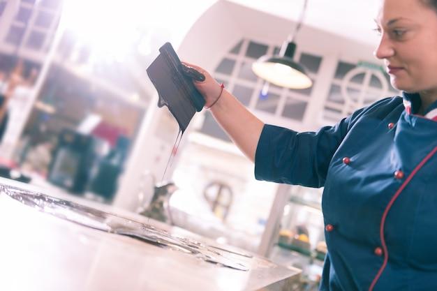 Donna soddisfatta. donna lavoratrice dai capelli scuri che si sente soddisfatta nel processo di produzione del cioccolato temperato