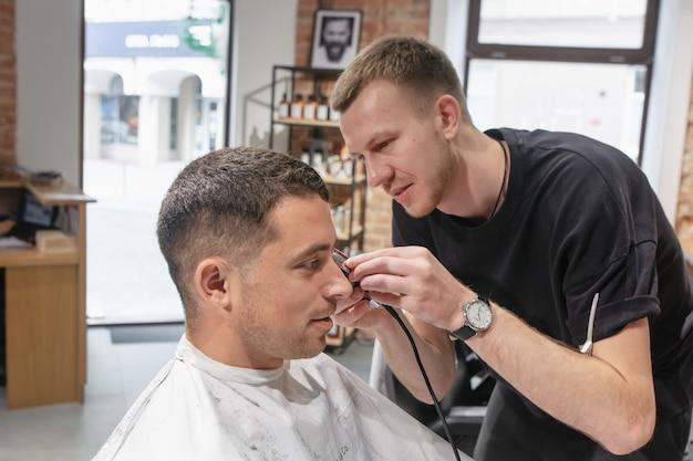 Giovane uomo caucasico soddisfatto che fa acconciatura nel negozio di barbiere.