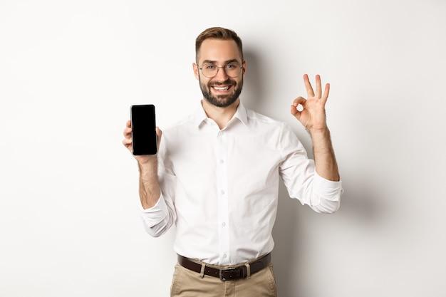 Giovane manager soddisfatto che mostra lo schermo dello smartphone e il segno ok, consigliando l'applicazione, in piedi su sfondo bianco.