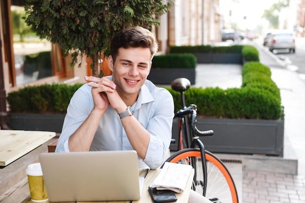 Giovane uomo alla moda soddisfatto in camicia che lavora al computer portatile