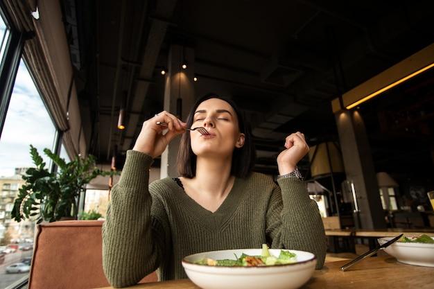 Giovane donna soddisfatta gode di una gustosa insalata in un ristorante, mettendo la forchetta in bocca e chiudendo gli occhi