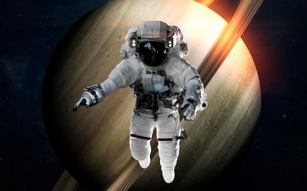Saturno con l'astronauta davanti al pianeta. sistema solare. elementi di questa immagine forniti dalla nasa