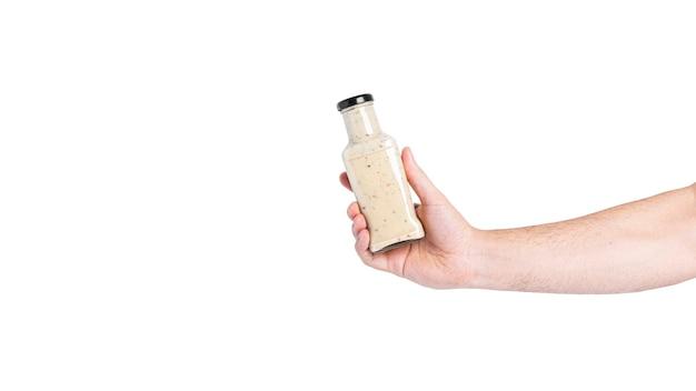 Salsa in bottiglia isolata su uno sfondo bianco. bottiglia in mano. foto di alta qualità