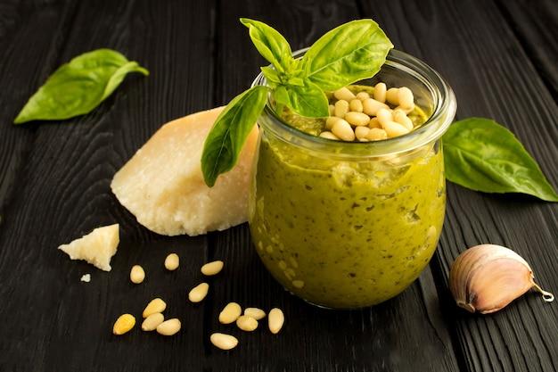 Condire il pesto nel barattolo di vetro e gli ingredienti