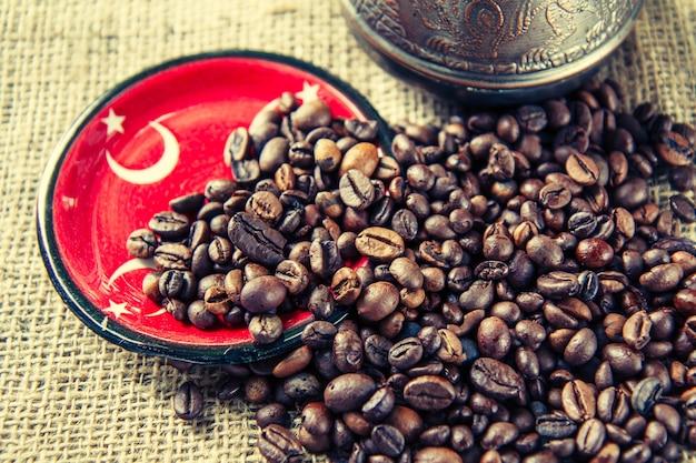 Piattino con elementi di bandiera turca, chicchi di caffè e caffettiera in rame su tela di sacco