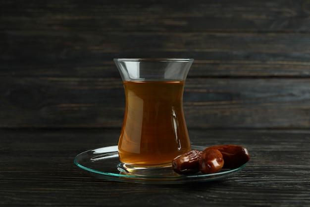 Piattino con bicchiere di tè e datteri su una superficie di legno