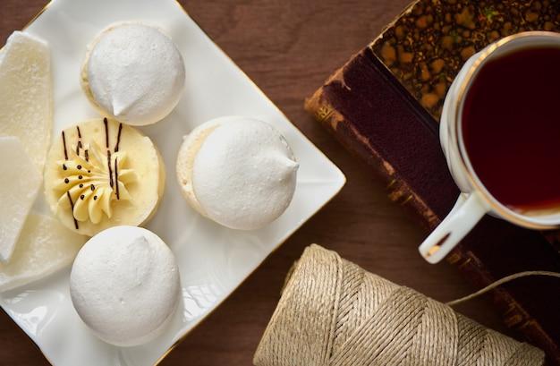 Piattino con torta di meringa con crema una tazza di tè un vecchio libro e bobina di filo