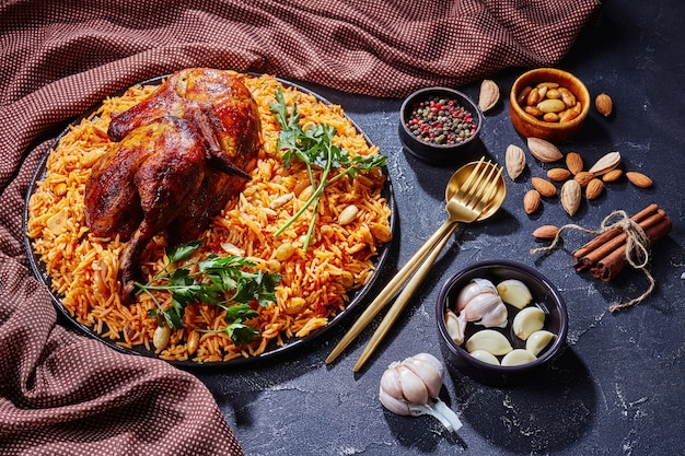 Kabsa dell'arabia saudita - quarto di pollo speziato e riso, mandorle tostate, uvetta e aglio su una piastra nera