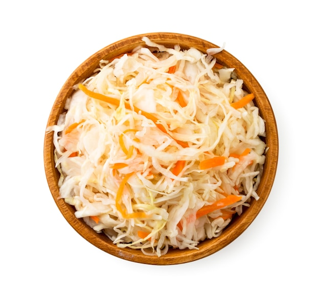 Crauti con carote in un piatto di legno su uno sfondo bianco. la vista dall'alto.