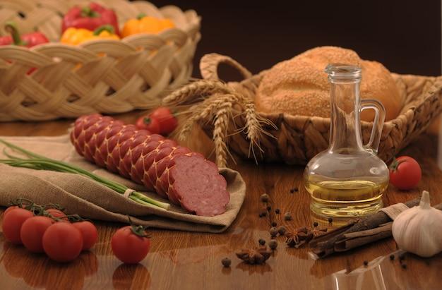 Salsiccia e pane in un cesto di vimini e verdure e aglio su un tavolo
