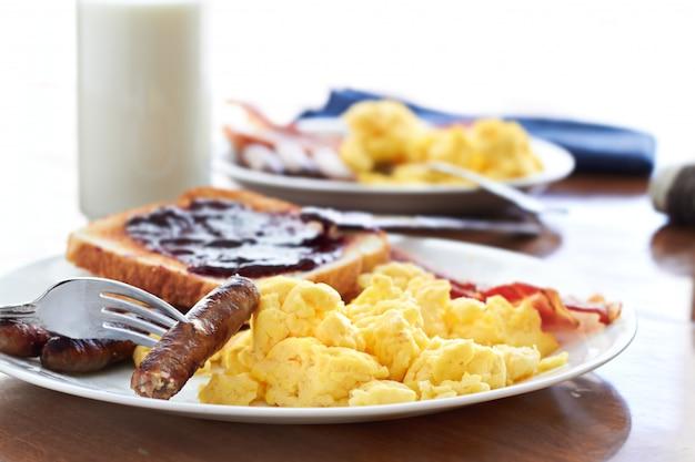 Legami di salsiccia raccolti da una forchetta durante una colazione abbondante.