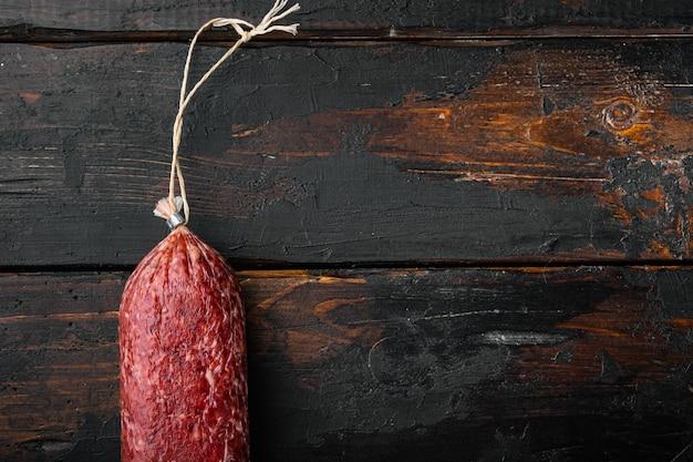Insieme di salame di salsiccia, su vecchio tavolo di legno scuro, vista dall'alto piatta