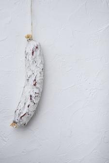 Salchichon di salsiccia sul tavolo bianco.
