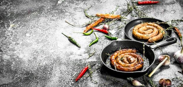 Salsiccia con erbe e spezie in padella. su fondo rustico.