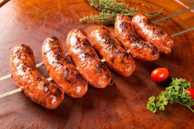 Salsicce allo spiedo barbecue su uno spazio di legno