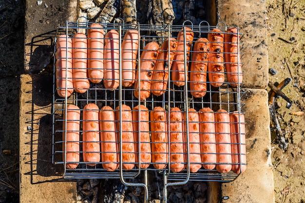 Salsicce che cucinano in una griglia del barbecue sul fuoco di accampamento