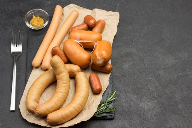 Salsicce di diverse varietà su carta forchetta di senape in una ciotola di vetro