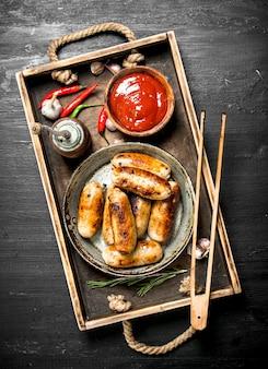 Salsicce in padella con salsa sul vassoio in legno sulla lavagna nera.