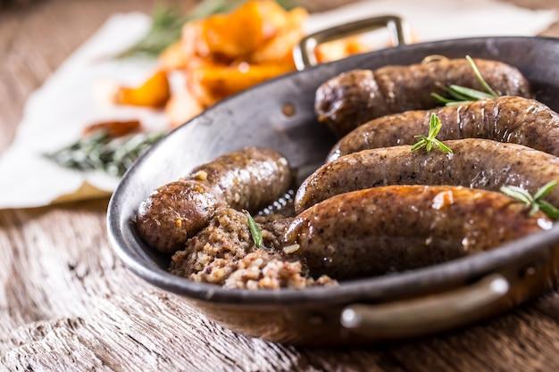 Salsicce.salsiccia di maiale arrosto in padella con patate e rosmarino.