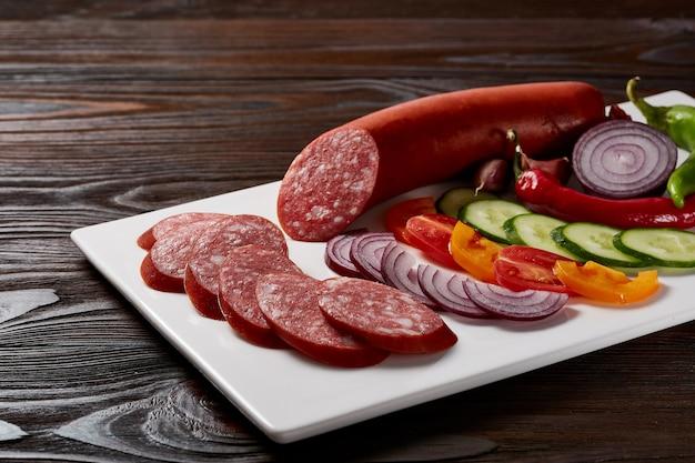 Salsicce con contorno di verdure ed erbe aromatiche con salse e pane su un piatto rettangolare bianco su un tavolo di legno scuro.