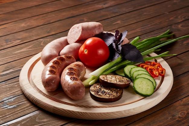 Salsicce con contorno di verdure ed erbe aromatiche con salse e pane su un piatto di legno su un tavolo di legno scuro.