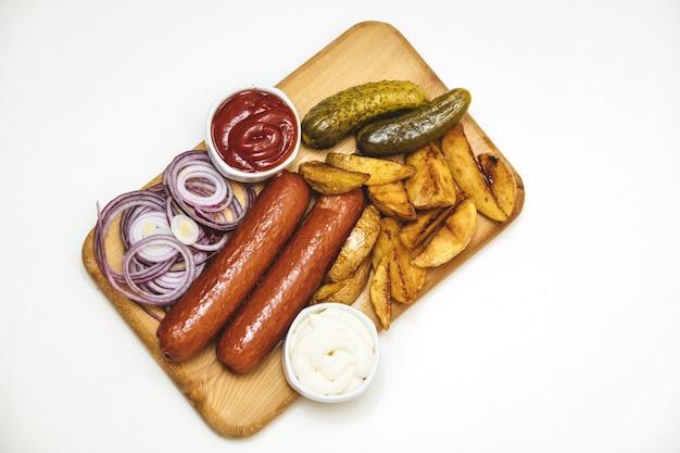 Salsicce con patate arrosto, salse, cipolle e cetrioli sottaceto su tavola di legno su sfondo bianco vista dall'alto
