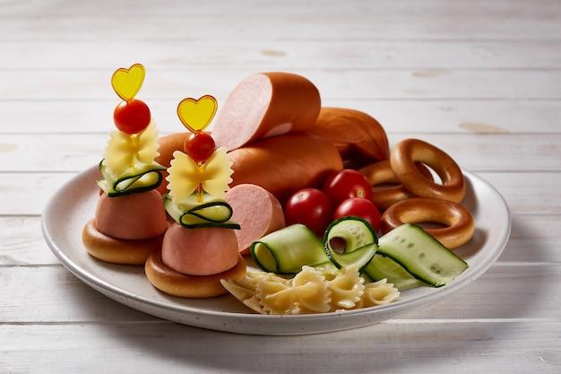 Salsicce con verdure ed erbe aromatiche guarnire con salse e pane su un piatto in ceramica grigia su un tavolo di legno bianco.