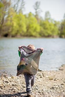 Salvare il concetto di ambiente, un ragazzino che raccoglie immondizia e bottiglie di plastica sulla spiaggia da buttare nella spazzatura.