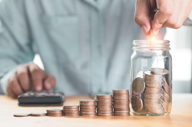 Risparmia denaro e concetto di investimento, uomo d'affari che mette moneta al barattolo di risparmio con monete impilate e utilizza la calcolatrice,